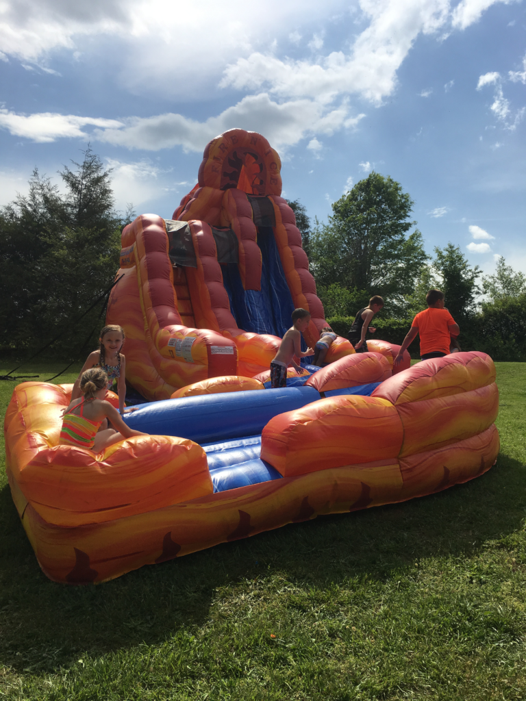children playing on inflated Fire and Ice Wet/dry slide at an outdoor event